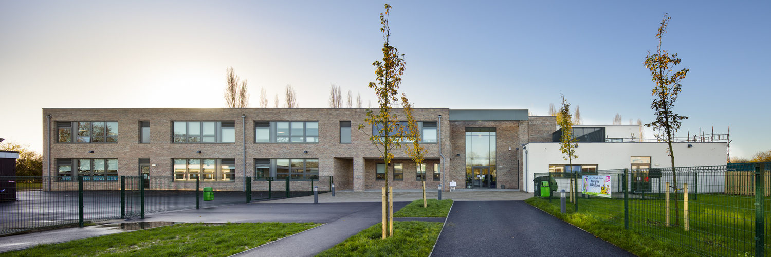Canterbury Primary School is one of thirteen schools in Kent to be rebuilt through the first phase of the Priority Schools Building Programme (PSBP). Designed by Ellis Williams Architects and built by Wates Construction, the new two storey building was constructed using the Wates ADAPT design. This is a standardised school solution which uses simple, robust materials and principles, along with an integrated building services solution to create high quality, light and airy classrooms suitable for modern teaching. The standardisation of the layouts, design components and materials reduce the build time and cost of delivery, whilst still allowing for flexibility and variety in the school design. At Canterbury, the standard design was changed to incorporate two large light wells in the building and more brickwork detail on the outside. The new school comprises thirteen classrooms, a new hall, kitchen with server, learning resource centre, plus a staff room and administrative offices and a car park area. Client: Education Funding Agency (EFA). Main Contractor: Wates Construction / Wates Group. Architect: Ellis Williams Architects (EWA). Structural Engineer: BWB. Services Engineer: CSD. Client PQS: Mott McDonald. Other parties: Prima Systems Ltd, Priority Schools Building Programme (PSBP), Department for Education (DfE).